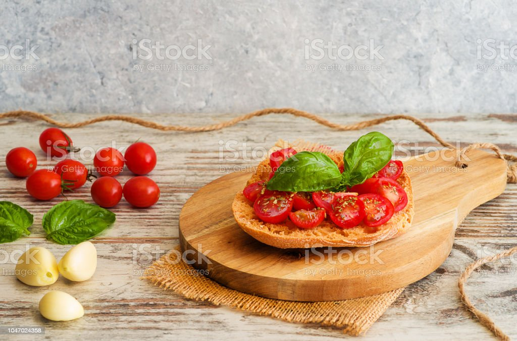 Fresh tomato bruschetta with basil and garlic on rustic background. - foto stock