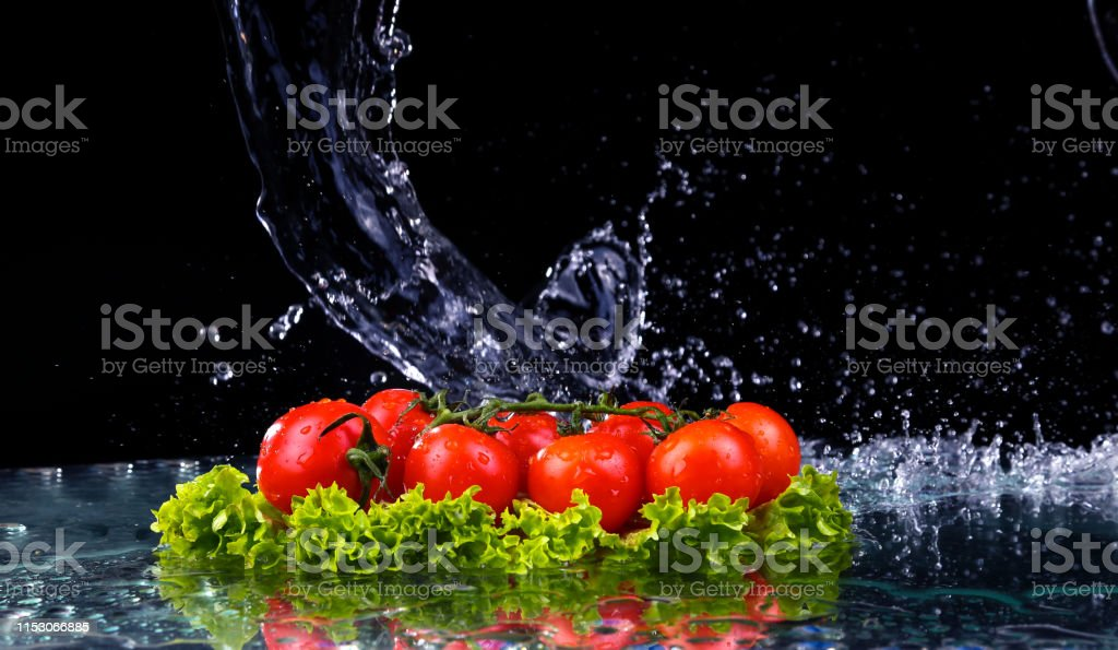 Fresh tomato cherry and green fresh salad with water drop splash on...