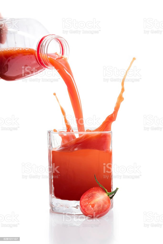 Fresh tomato juice being poured from bottle stock photo