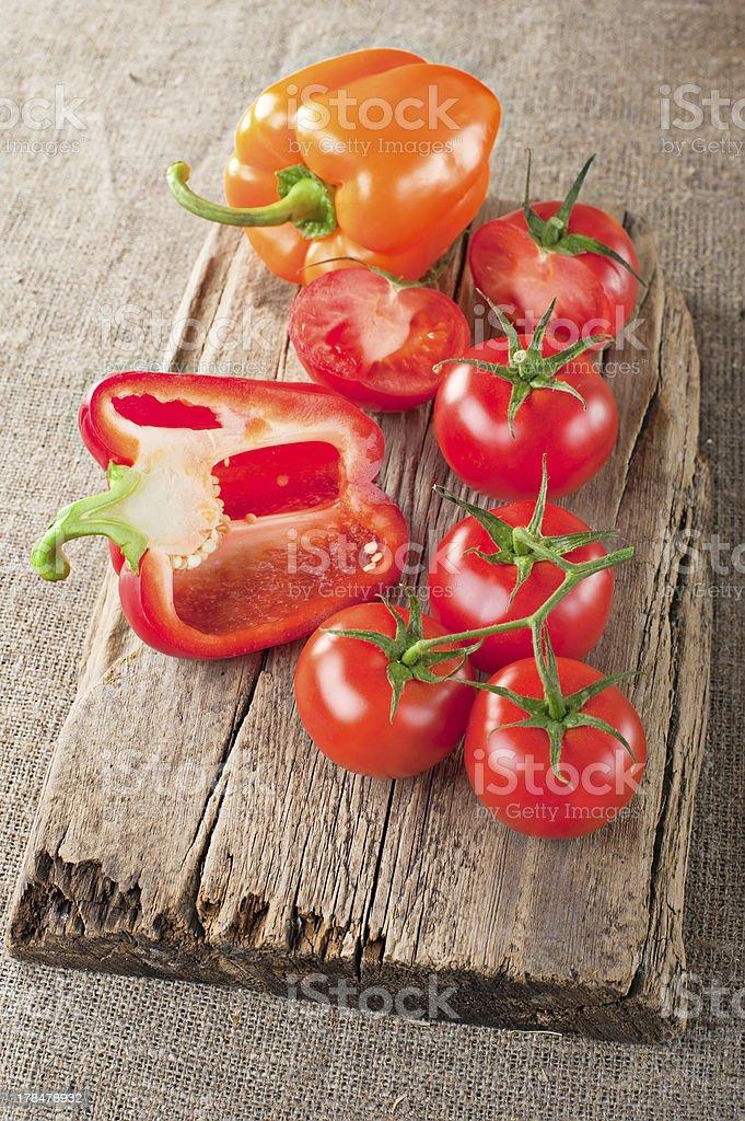 Fresh tomato, paprika on vintage wooden cutting board royalty-free stock photo
