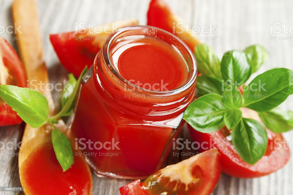 Fresh tomato sauce with basil on wooden table stock photo