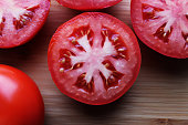 Top view of fresh tomato slices on bamboo background