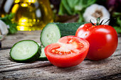 Fresh sliced tomatoes and cucumber on wooden table - vegetable, vegetarian food