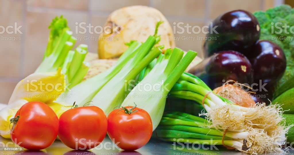 Fresh tomatoes, eggplants, lattuce and onion on the counter stock photo