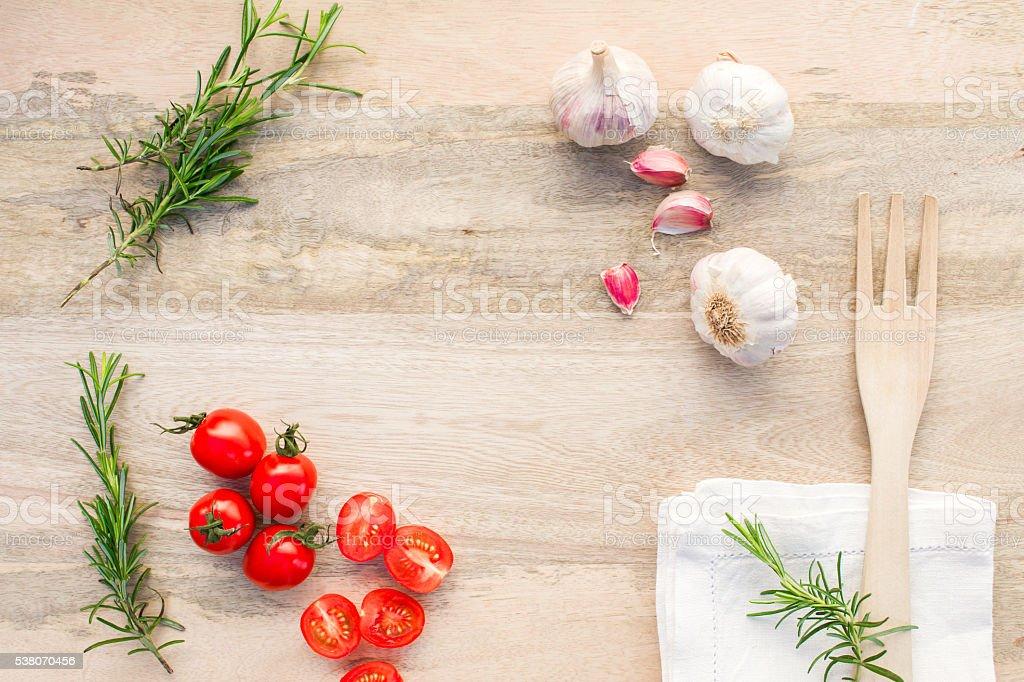 Frische Tomaten, Knoblauch und Rosmarin auf Holz Tisch.   – Foto