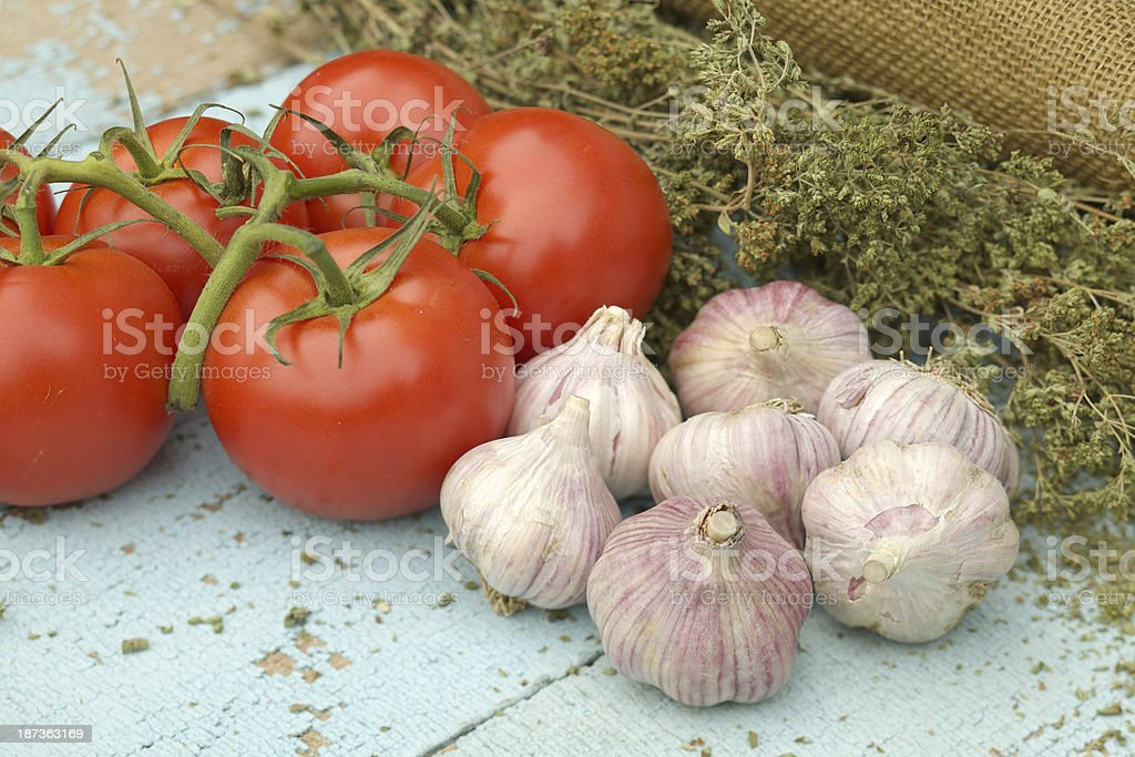 Fresh tomatoes, garlic bulbs and dried oregano royalty-free stock photo