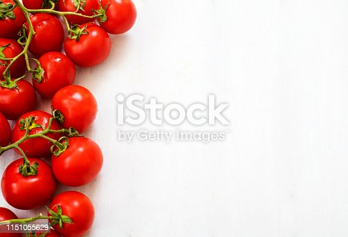 Fresh tomatoes in a plate on wood background. Harvesting tomatoes. Top view