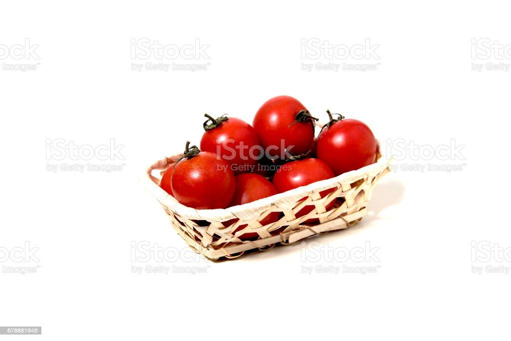 Beyaz bir arka plan üzerinde tahta bir sandık içinde asma üzerinde taze domates royalty-free stock photo