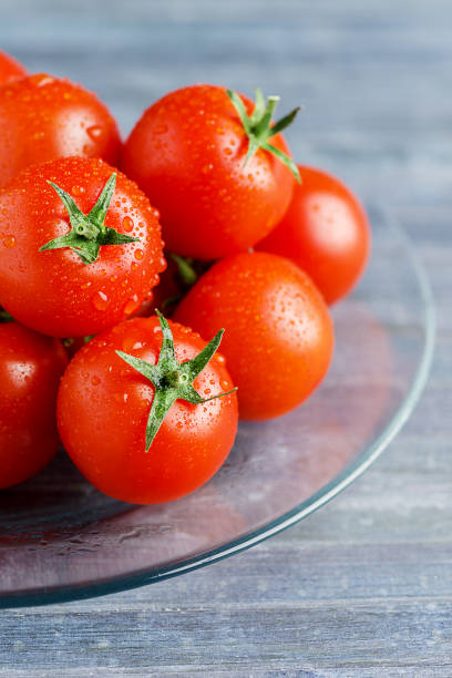 Fresh tomatoes on trasparent dish on wooden blue background - foto stock