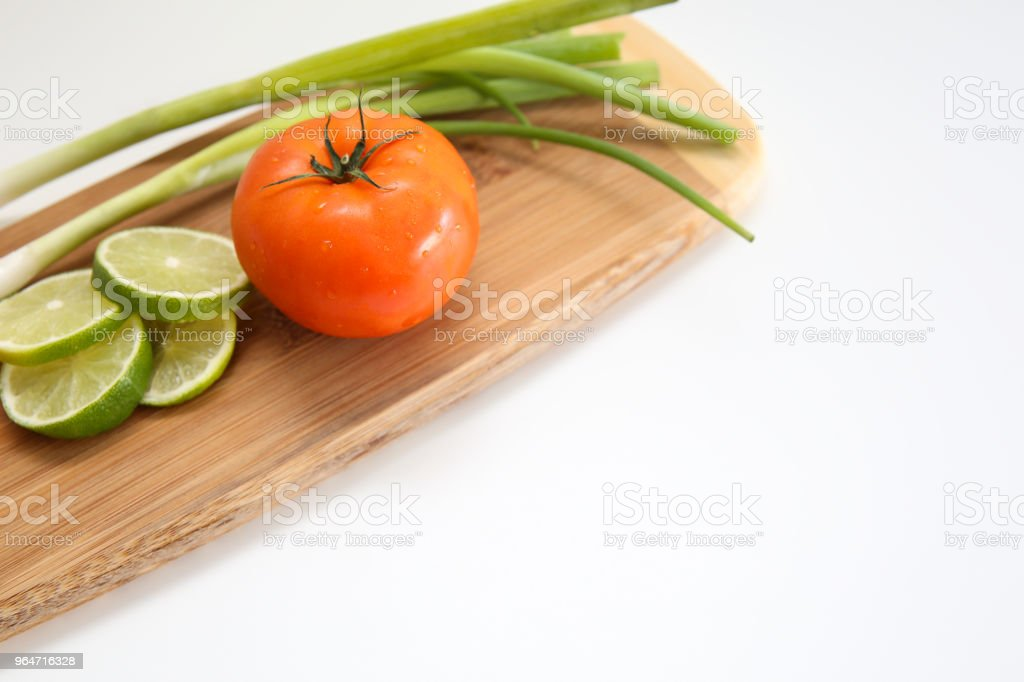 Fresh tomatoes, sliced limes, and chives royalty-free stock photo
