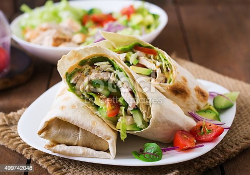 istock Fresh tortilla wraps with chicken and fresh vegetables on plate 499742048