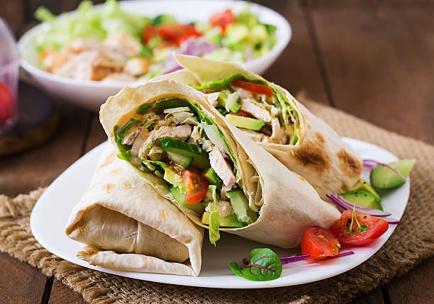 fresh tortilla wraps with chicken and fresh vegetables on plate - tortilla stock photos and pictures
