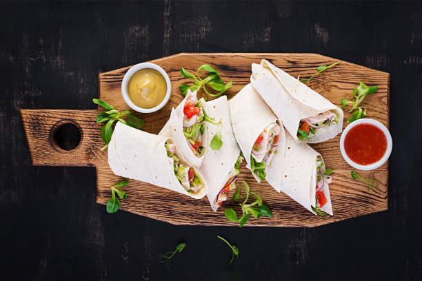 Frische Tortilla wickelt mit Huhn und frischem Gemüse auf Holzbrett. Huhn Burrito. Mexikanische Küche. Gesundes Ernährungskonzept. Mexikanische Küche. Top-Ansicht, Overhead – Foto