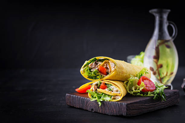 Fresh tortilla wraps with chicken and fresh vegetables on wooden board. Chicken burrito. Mexican cuisine. Copy space stock photo