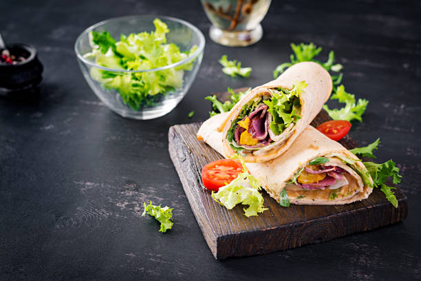 Fresh tortilla wraps with ham beef and fresh vegetables on wooden board. Beef burrito. Mexican cuisine. Copy space stock photo