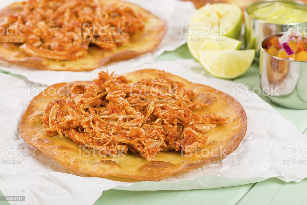 Fresh tostadas sitting on a green table with limes behind it stock photo