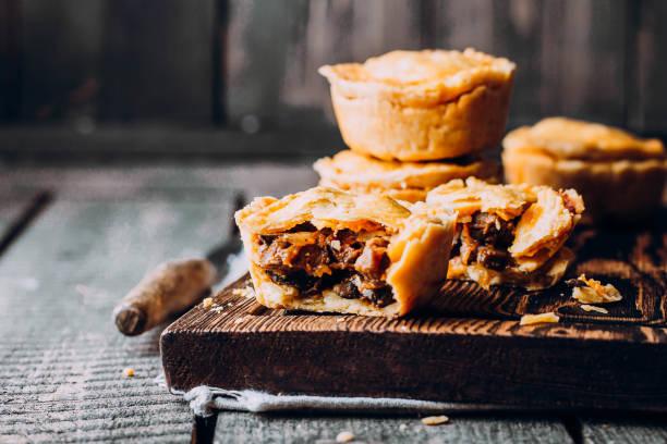 mini torta de carne australiana tradicional fresca na placa de madeira no fundo da tabela, closeup com espaço de cópia, de estilo rústico - torta salgada - fotografias e filmes do acervo