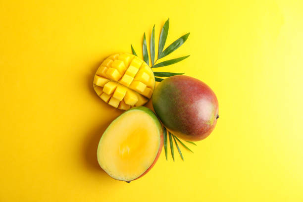 Fresh tropical ripe mango on color background, top view Fresh tropical ripe mango on color background, top view mango stock pictures, royalty-free photos & images