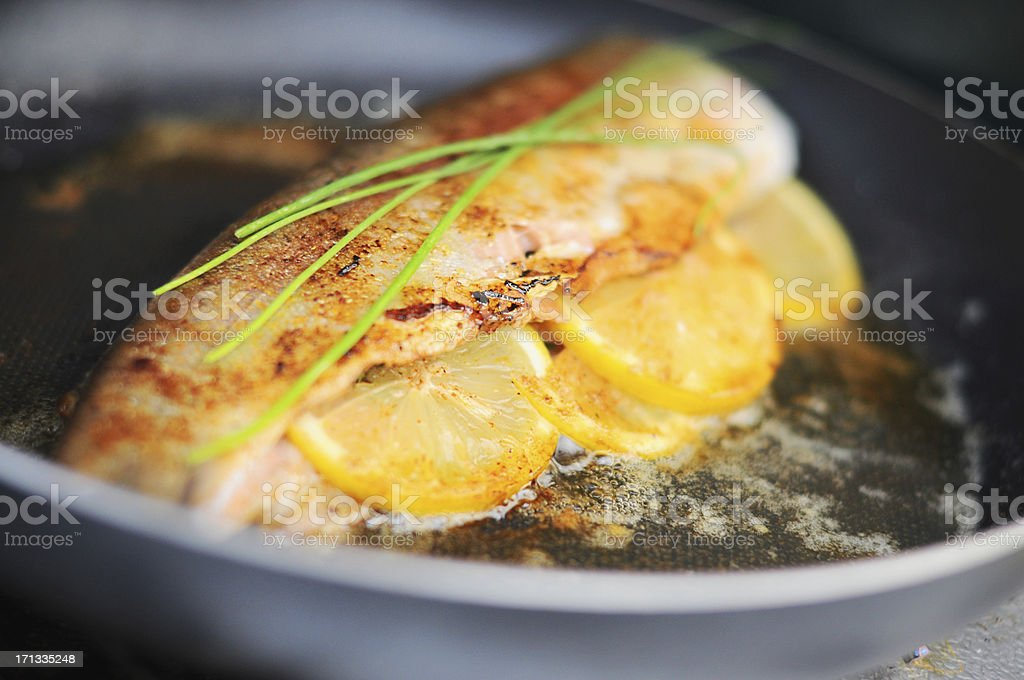 Fresh trout cooking in skillet stock photo