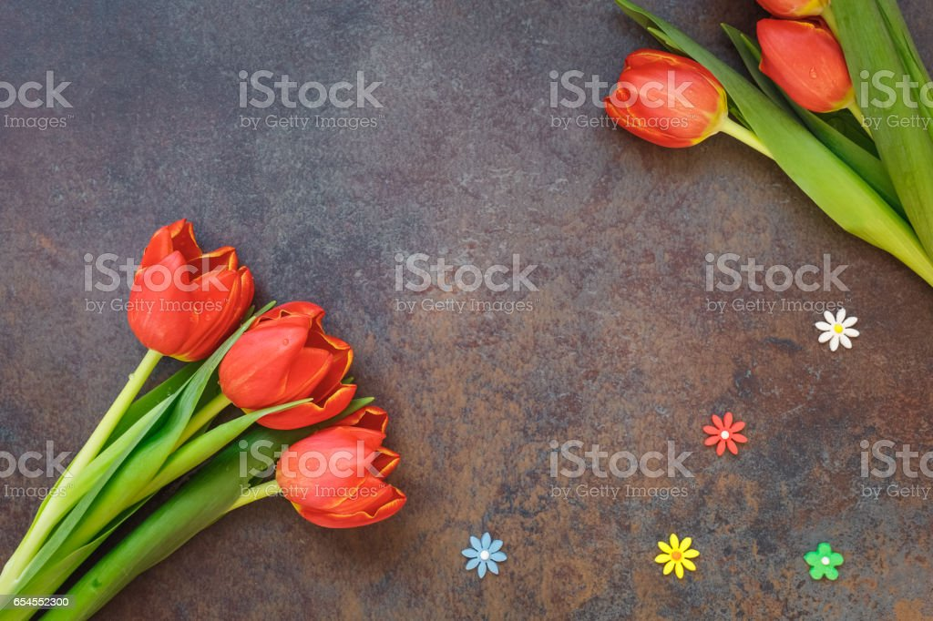 Fresh tulips with flower sprinkles on stone table stock photo
