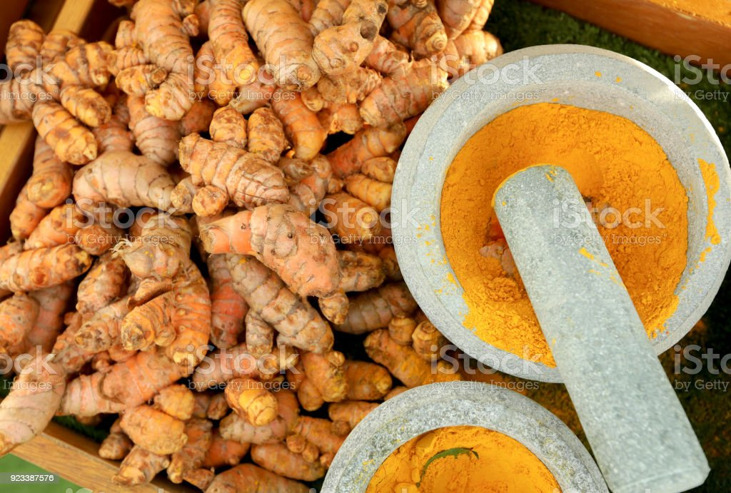 fresh-turmeric-roots-and-turmeric-powder-in-mortar-picture-id923387576