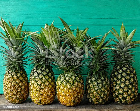 A fresh colorful two-headed tropical pineapple standing in the center of a row of other pineapples on a rustic wooden table against a turquoise wooden walled background.  Some copy space above the fruit.