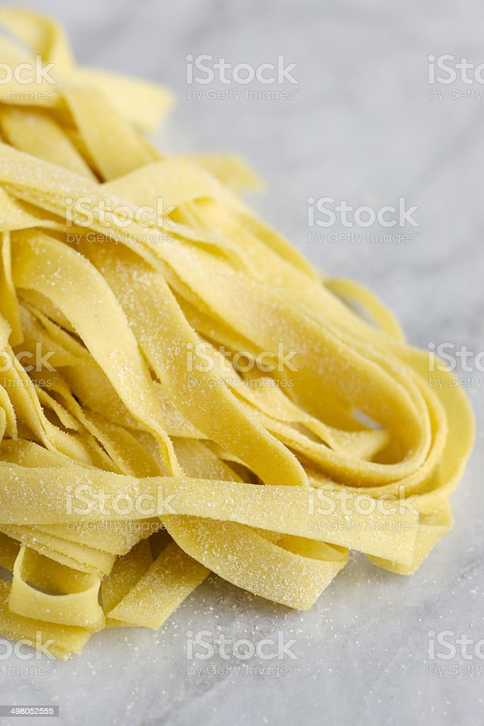 Fresh uncooked linguine pasta on marble royalty-free stock photo