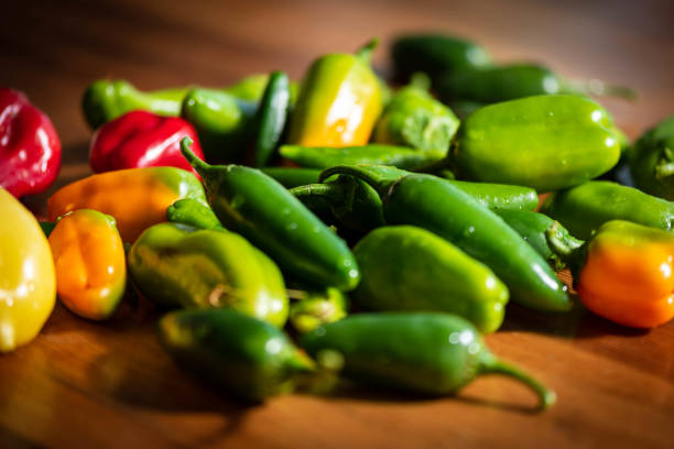 Fresh variety of green, red, orange and yellow peppers on the wooden background.