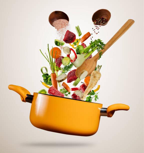 Légumes frais et viandes dans une marmite de vol sur fond gris - Photo