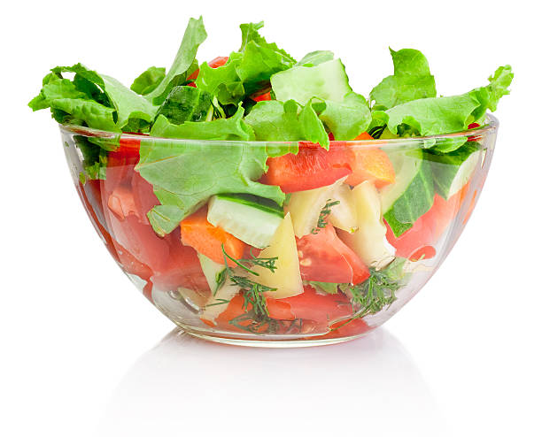 Fresh vegetable salad in transparent bowl isolated on white stock photo