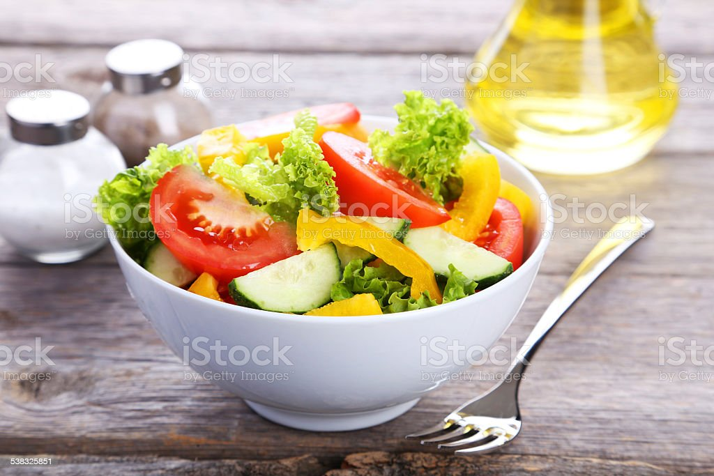 Fresh vegetable salad on grey wooden background stock photo