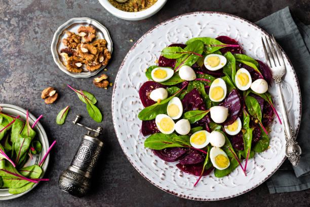 salat aus frischem gemüse mit gekochten rüben, mangold-blätter, walnüsse und wachteleier - wachtelei stock-fotos und bilder