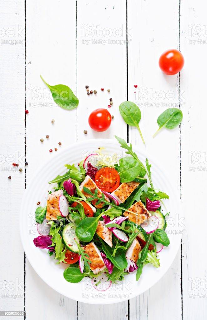 Salat aus frischem Gemüse mit gegrillter Hähnchenbrust - Tomaten, Gurken, Rettich und Mix Salatblätter. Hähnchen-Salat. Gesunde Ernährung. Ansicht von oben – Foto