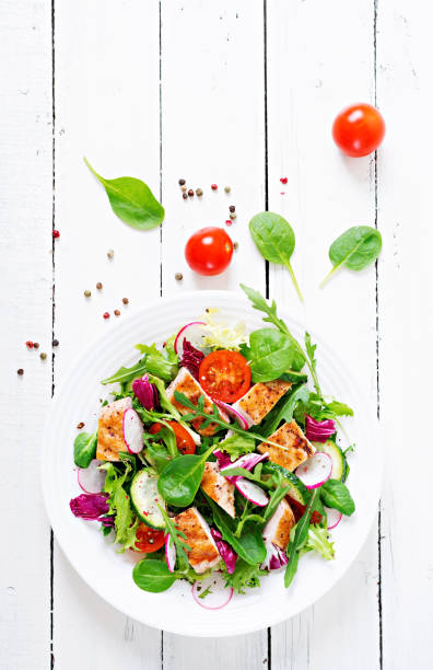 Fresh vegetable salad with grilled chicken breast   - tomatoes, cucumbers, radish and mix lettuce leaves. Chicken salad. Healthy food. Top view stock photo