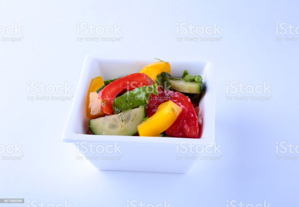 fresh vegetable salad with tomato, cucumber, bell pepper and lettuce leaf in white bowl. stock photo