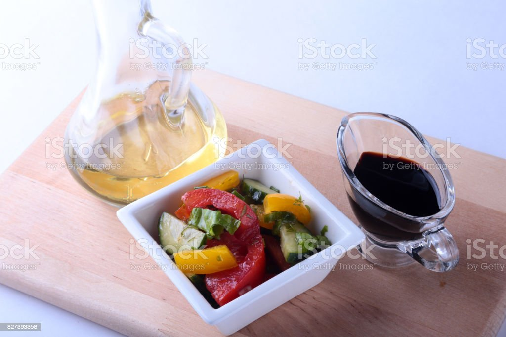 fresh vegetable salad with tomato, cucumber, bell pepper, lettuce leaf in white bowl, olive oil and balsamic souce in bottle. Selective focus. stock photo