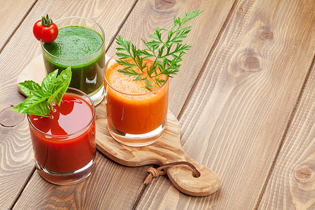 Fresh vegetable smoothie. Tomato, cucumber, carrot Fresh vegetable smoothie on wooden table. Tomato, cucumber, carrot. View with copy space vegetable juice stock pictures, royalty-free photos & images