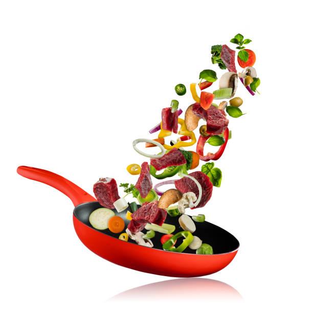 verse groenten en rundvlees vliegen in een pan op witte achtergrond - pan keukengereedschap stockfoto's en -beelden