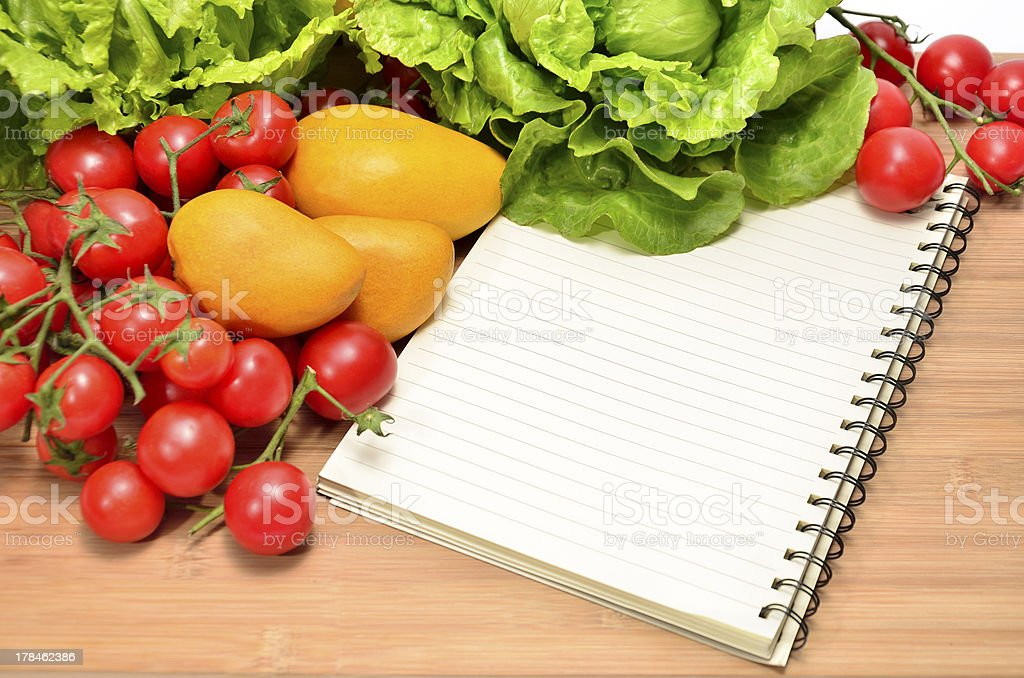 Fresh vegetables and blank recipe book stock photo