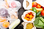 Fresh vegetables and fruits in eco cotton bags against vegetables in plastic bags. Zero waste concept - Use plastic bags or multi-use bags. Zero waste, green and conscious lifestyle concept