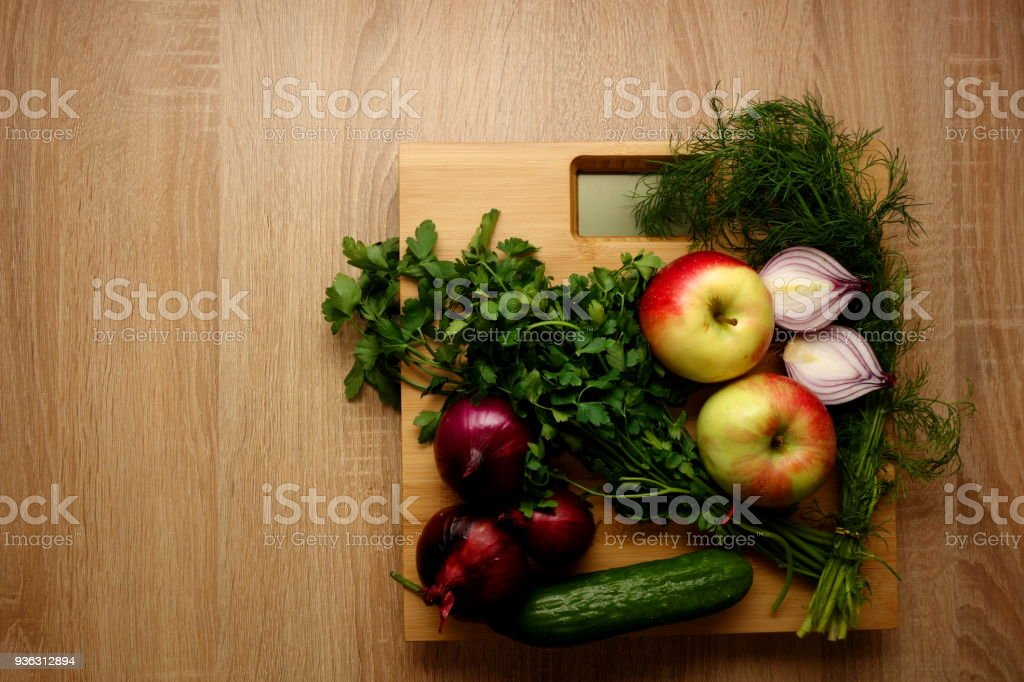 Fresh vegetables and fruits on bathroom scale stock photo
