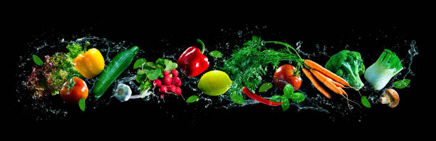 Fresh vegetables and water splashes on panoramic background stock photo