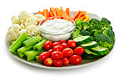 Fresh vegetables arranged on a platter with dip