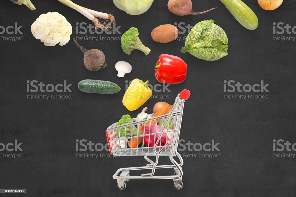 Fresh vegetables fall in market cart. Dark surface in backgorund. stock photo