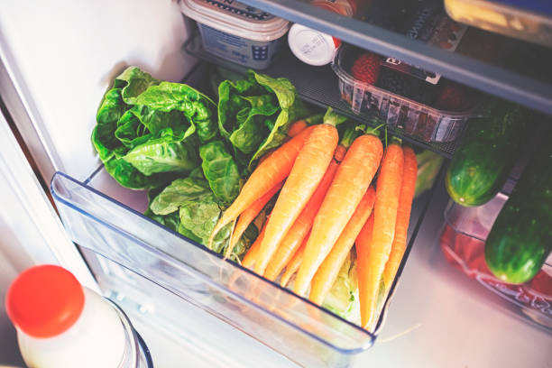 Fresh vegetables for storage in the fridge in a plastic box stock photo