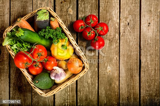 View directly above of a bunch of fresh vegetables in a basket and sitting on a weathered wooden table. Studio shot and plenty of copy space.