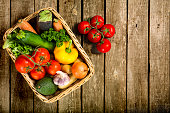 Fresh vegetables in a basket on a wooden table