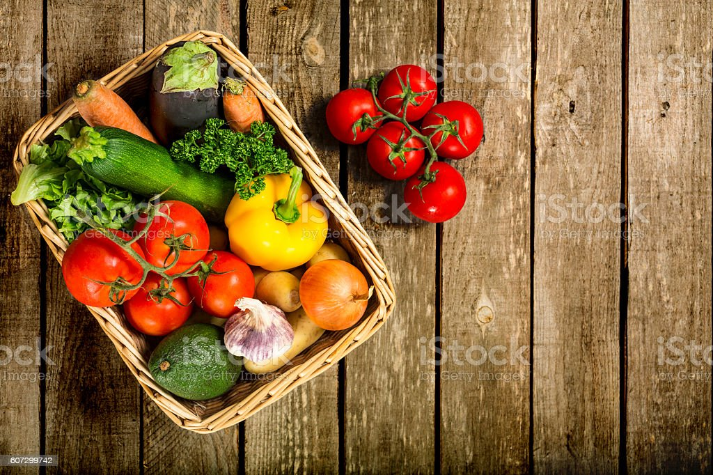 Fresh vegetables in a basket on a wooden table stock photo
