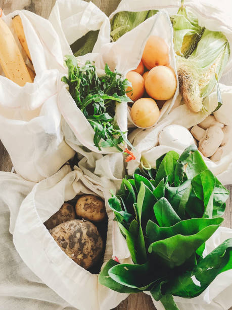 fresh vegetables in eco cotton bags on table in the kitchen. lettuce, corn, potatoes, apricots, bananas, rucola, mushrooms from market. zero waste shopping concept.   ban plastic - food delivery стоковые фото и изображения