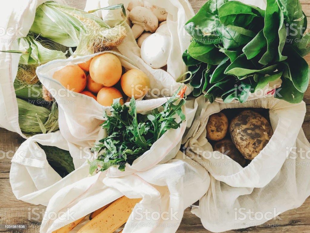 廚房裡餐桌上的環保棉袋中的新鮮蔬菜。生菜, 玉米, 馬鈴薯, 杏, 香蕉, rucola, 蘑菇市場。零垃圾購物概念。  禁止塑膠 - 免版稅人造物件圖庫照片